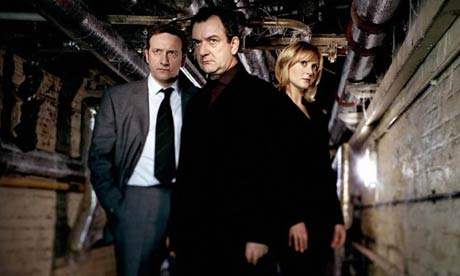 Hunting serial killers - a grim, serious business, set in grim, serious dingy basements. (Crack a smile and we'll have to do the photo again.)